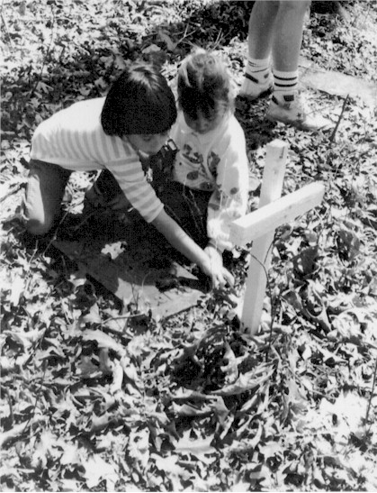 children looking at gravestone