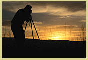 [Photograph]: A photographer is taking a picture of the sunset.