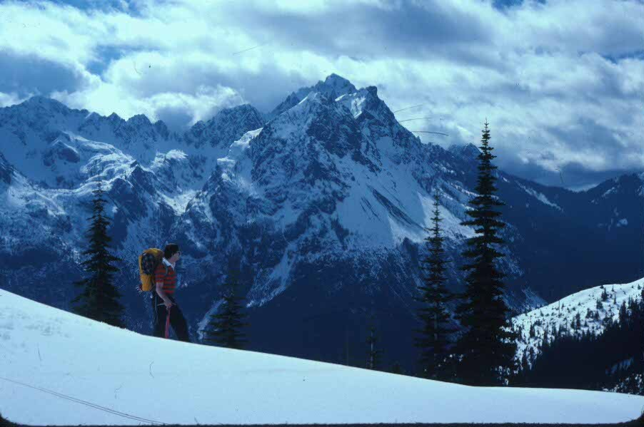 A snowshoer enjoys a panoramic view of Mount Pershing.