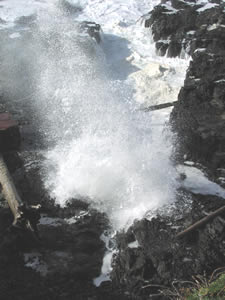 photo of wave exploding against rocks at Devils Churn