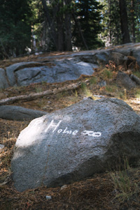 On August 24 1849 a group of Mormon travellers called the Odd Fellows stopped and left their marks in Carson Pass.  This photograph shows one of many white signatures left on the granite stones.  Home  is printed across the face of this boulder next to a series of three linked rings a symbol of the Odd Fellows. Photography by Amy L. Reid.