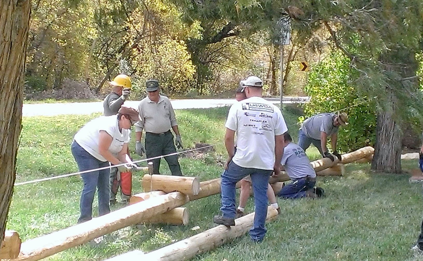 Photo of a volunteer hammering a nail while others are working on the fence.