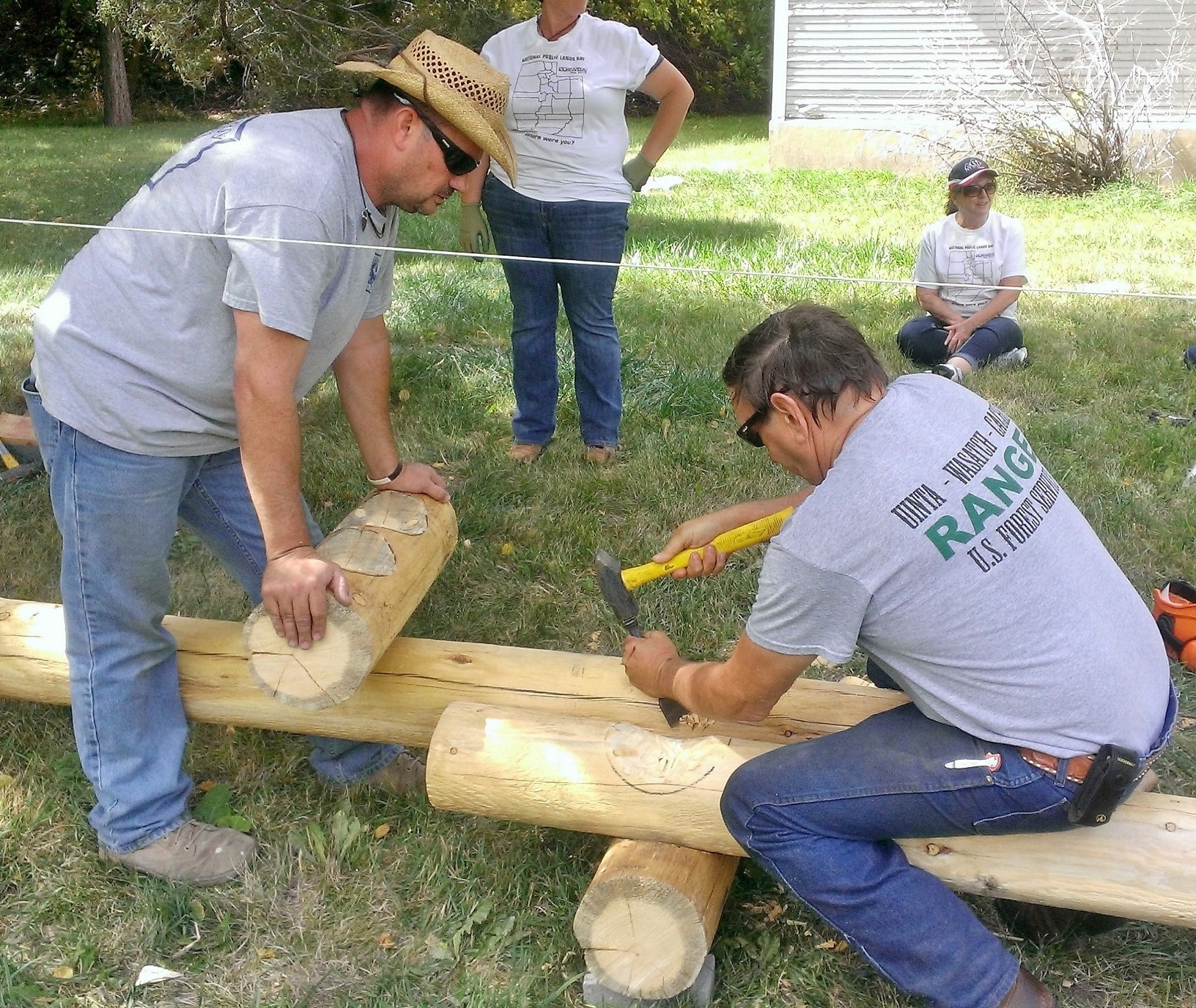 Photo of a volunteer chiseling out a joint for a log connection.