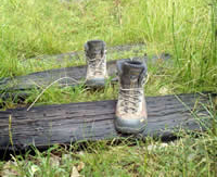 Photo of hiking boots sitting on railroad ties in the grass