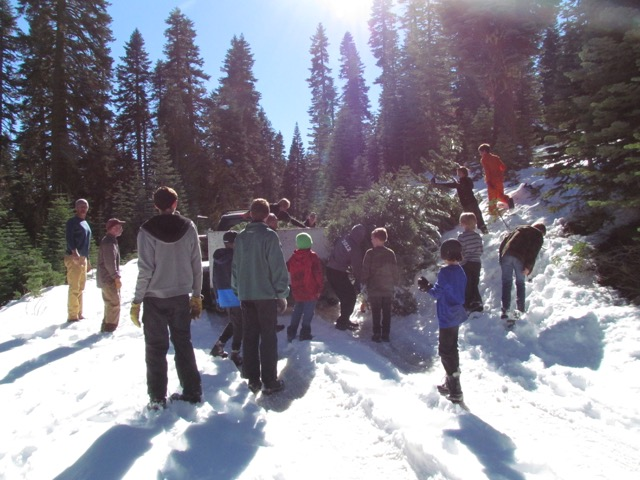 Boy Scouts and parents standing around a truck in the snow, for a safety briefing