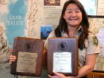 A woman holds two award plaques and smiles for a photo.