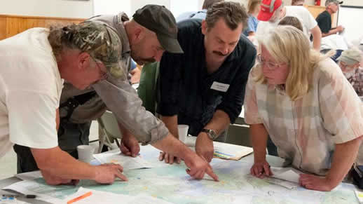 Four people looking at a map on a table