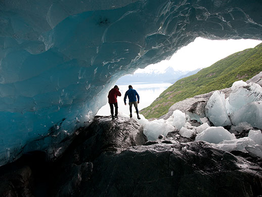 Two figures in the background stand under an arch of glacial ice.