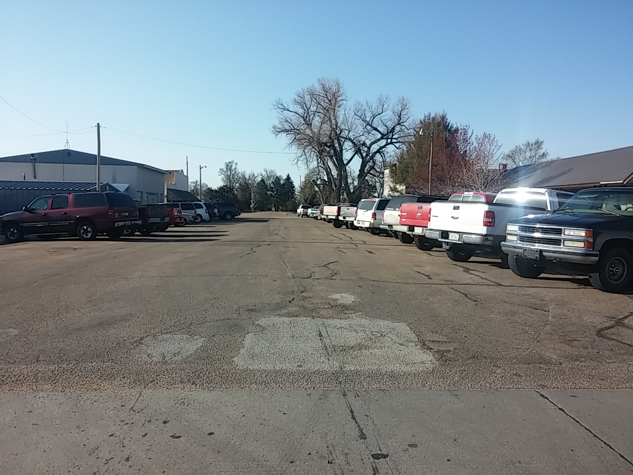 Shows a row of cars parked downtown for a pancake feed