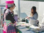 A woman in a brightly colored, native dress speaks to a woman behind a table at an information booth