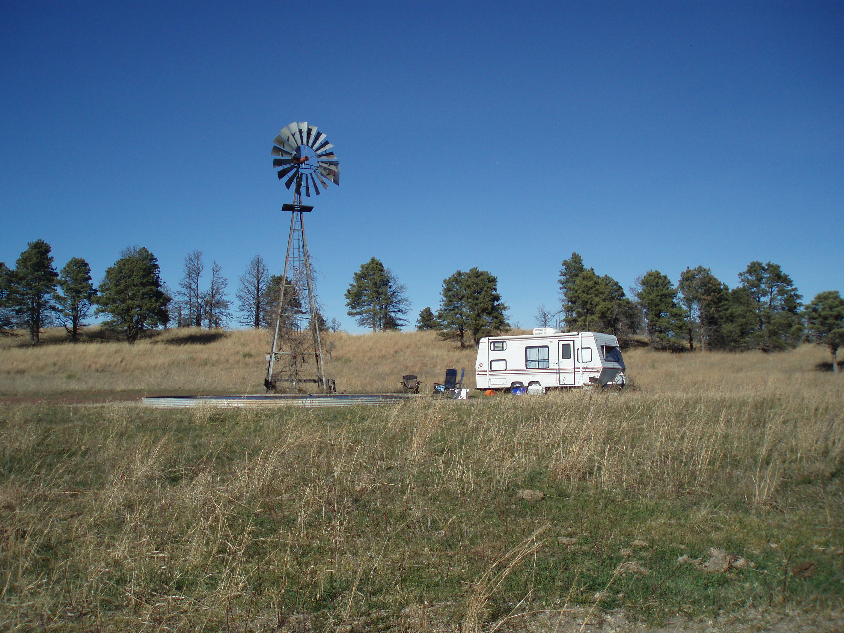 A small RV camped next to a windmill during deer season.