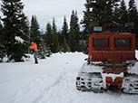 Shows technition measuring snow pack and an orange Snowcat used to access backcountry over snow