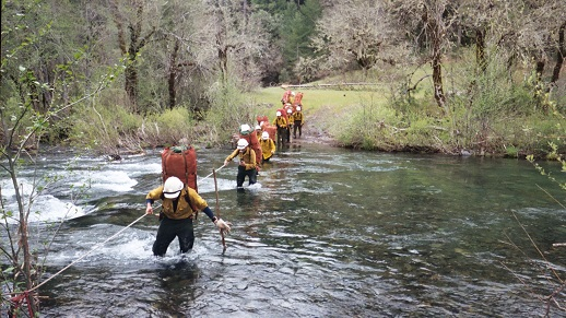 A crew of jumpers crosses a stream with their gear on their backs