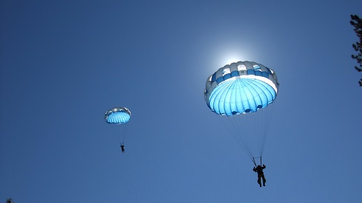 The sun shines through a parachute in the air as two smokejumpers float to the ground