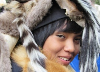 Photo of a native american boy with his headdress on.