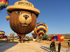 Photo of the Smokey Bear Hot Air Balloon resting on the ground at the festival.