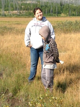 Photo of a Native American lady standing with a small child in a meadow.