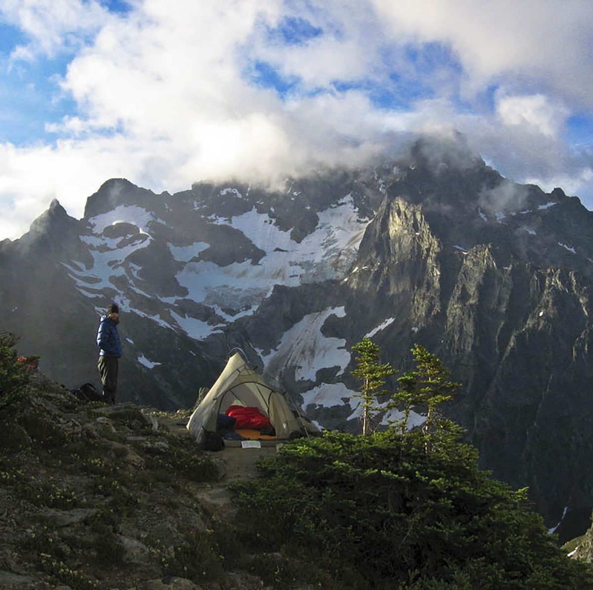 A man standing outside a tent on a mountain peak.
