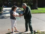 A Forest Service employee hands a seedling to a woman in front of an office.