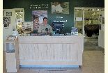 A smiling Forest Service employee behind the front desk of the Hudson-Meng Visitor's Center.