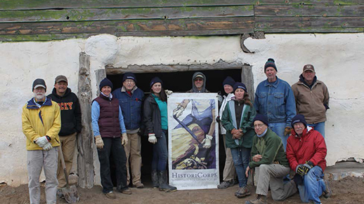 Group of people stand in front of a restored outbuilding
