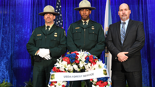 three law enforcement stand at attention behind a wreath of flowers
