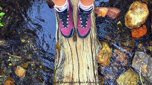 hiking boots on a log in a stream