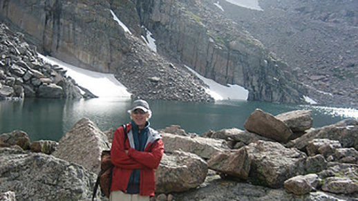 man standing in front of alpine lake