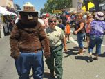 Smokey Bear is escorted down the busy street of a fair.