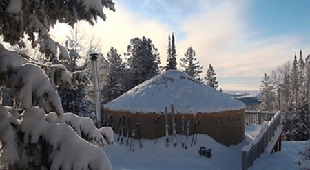 Photo of a yurt on a winter day with skis leaning against the side.
