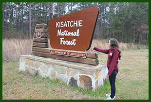 Girl pointing at Forest Service portal sign