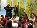 A Forest Service woman and Smokey Bear speak to kids.