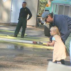 firefighters help little girl use fire hose