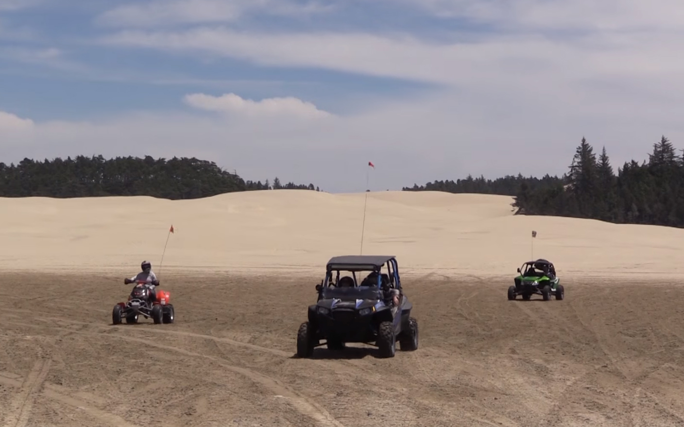 Three Off Road Vehicles on the Sand