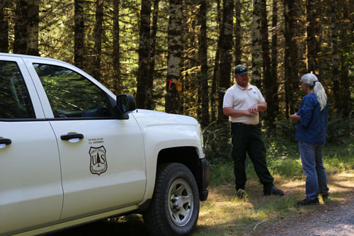 A forest service employee talking to a visitor outside of a forest service truck