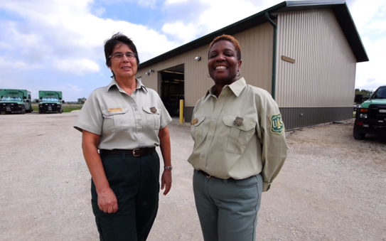 Two female employees standing outside of a maintenance building