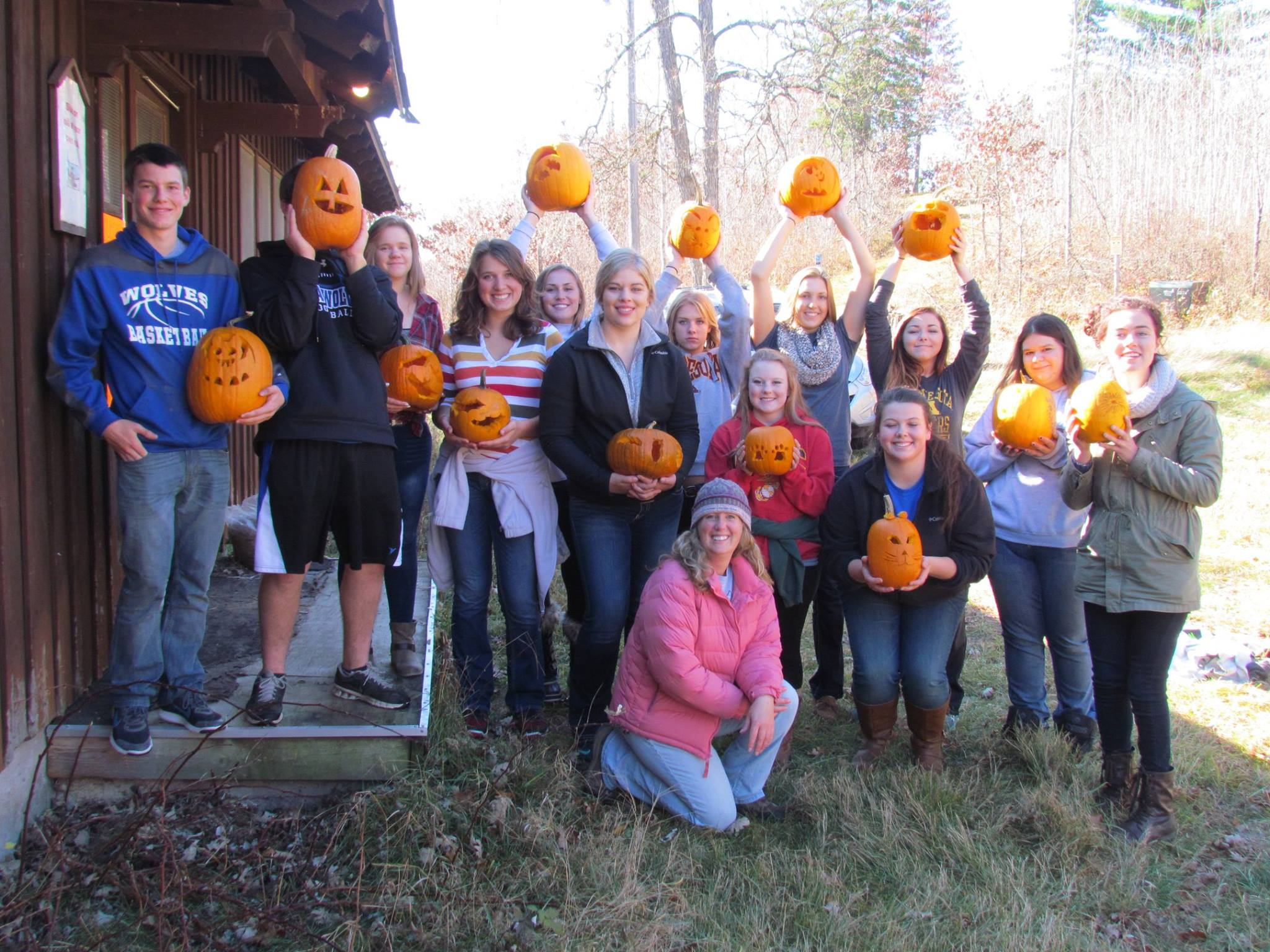 group of students at a halloween event all holding pumpkins