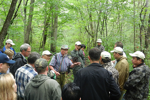 A large group of people in the woods listen to a central speaker.