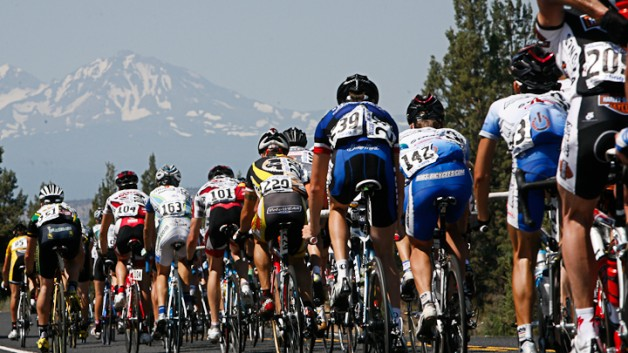 A large group of road cyclists racing with a mountain peak in the background