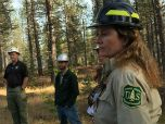 A female Forest Service employee stands in a crop of trees with people wearing hard hats.