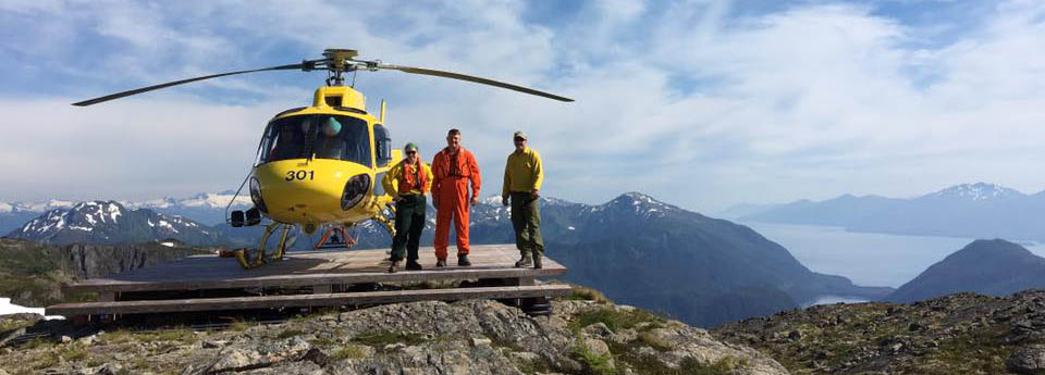 Helicopter Managers atop a mountain with yellow heliopter