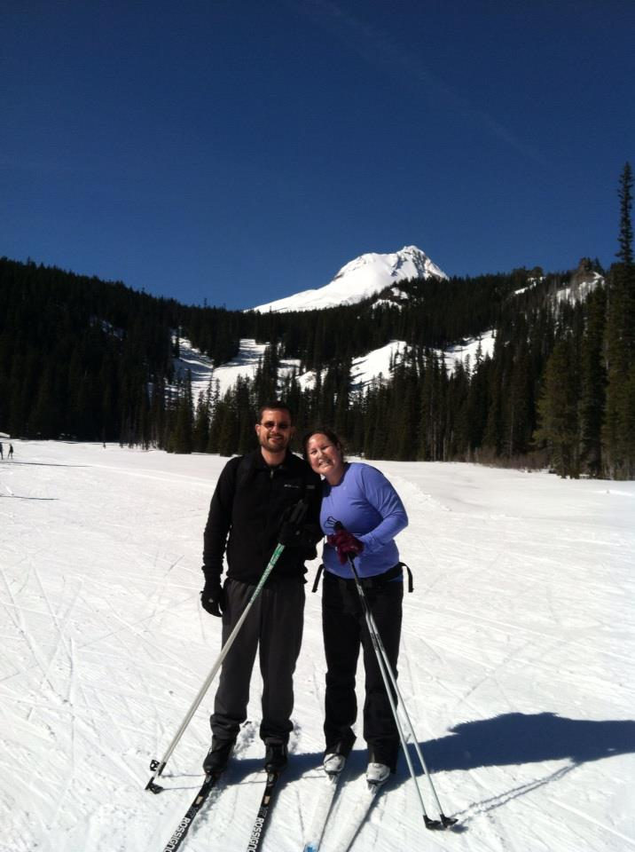Two cross country skiers with tree covered hills and a snow covered mountain peak behind them