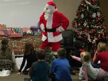 Santa Claus talks to a room full of children.