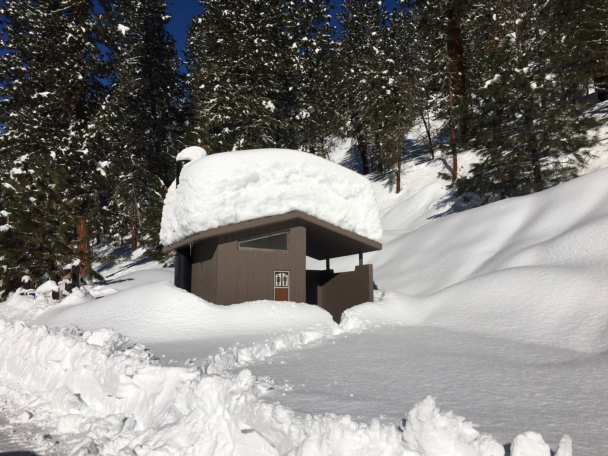 Photo of deep snow almost covering outhouse
