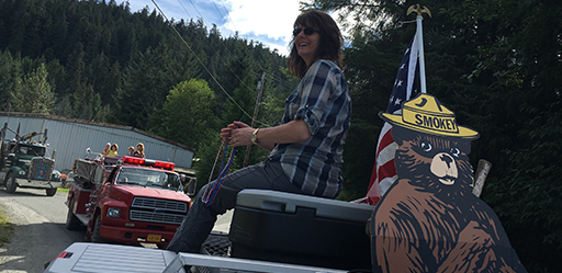 Acting Thorne Bay District Ranger Sandra Stevens atop the USFS Fire truck throwing red, white, and blue necklaces to the happy crowds.