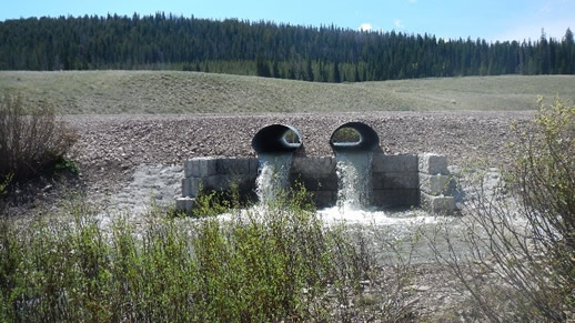 Photo of two culverts with water running out and falling into a creek.