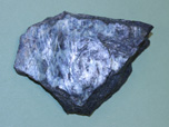 A serpentinite rock with flat polished, shiny and striated surface of green, white and purple