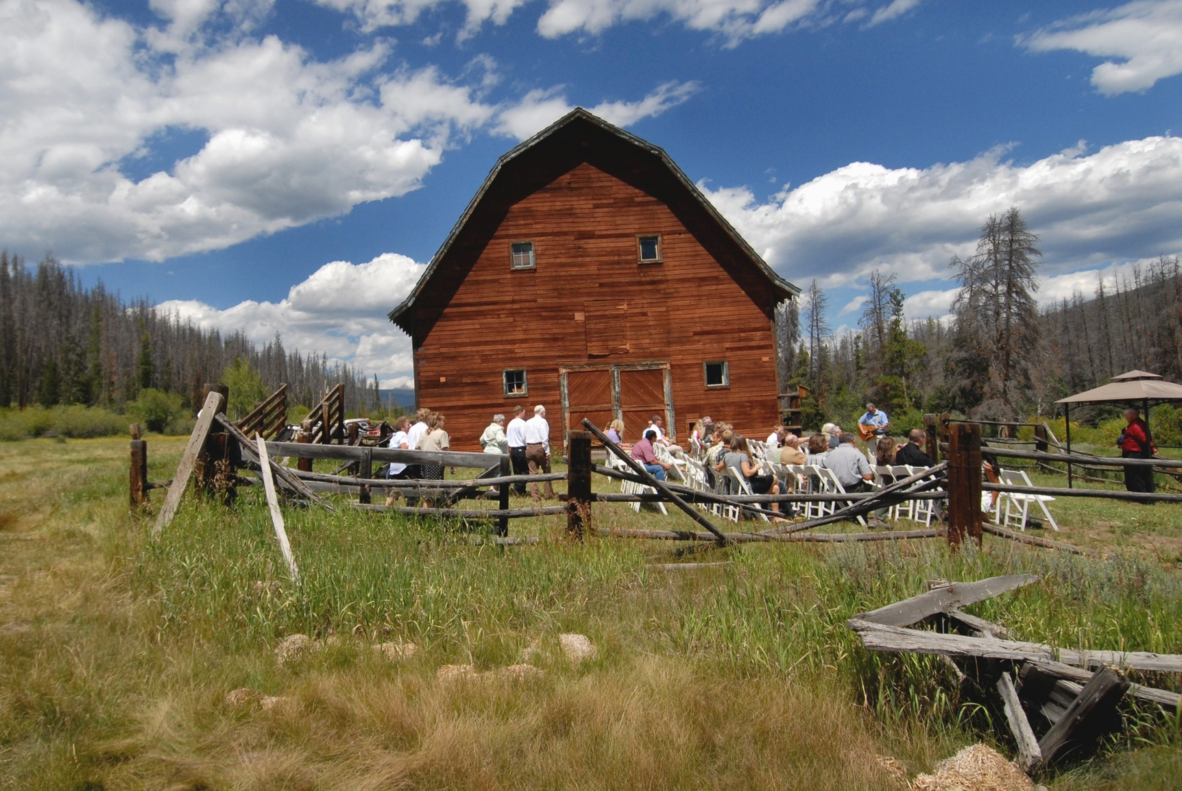Large brown wooden barn with rows of seats in front filled with wedding goers in the forest.