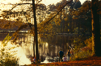Family fishing on the shore of Ratcliff Lake at sunset.
