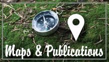 "A compass sits on green moss. Text reads ""Maps and Publications"""
